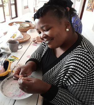 Person crafting beads and ribbons